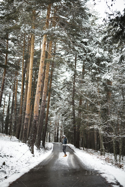 Side view of young person in stylish outfit standing on asphalt forest road on majestic winter day