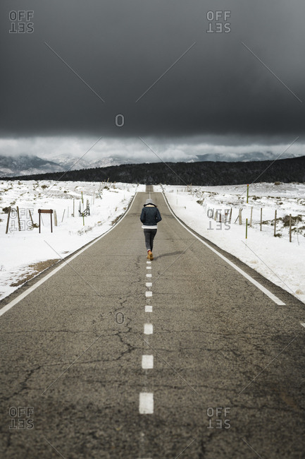 Back view of young person in stylish outfit walking in middle of asphalt road on cloudy winter day in beautiful countryside