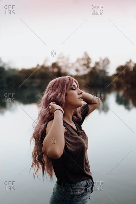 Side view of beautiful woman with long pink hair standing against tranquil lake with eyes closed
