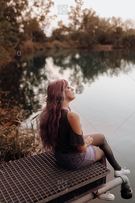Side view of sensual woman with pink hair sitting on pier above lake in peace