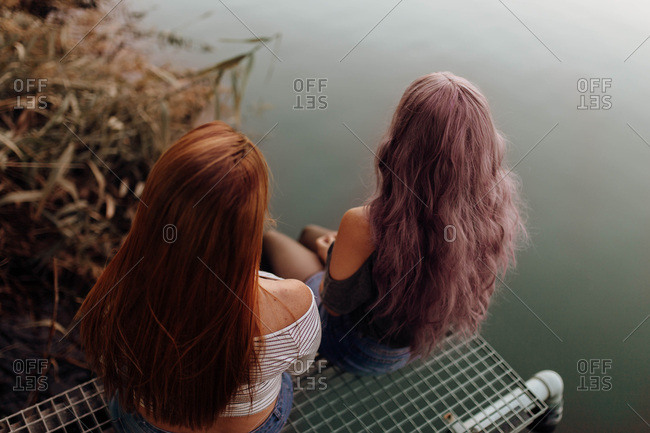 Form above back view of young women with long hair sitting together above water of tranquil lake