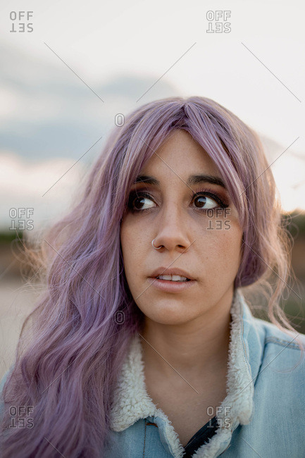 Young woman in casual outfit with long pink hair standing in high dry grass
