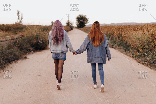 Back view of modern women in denim with long hair holding hands and walking on remote rural road