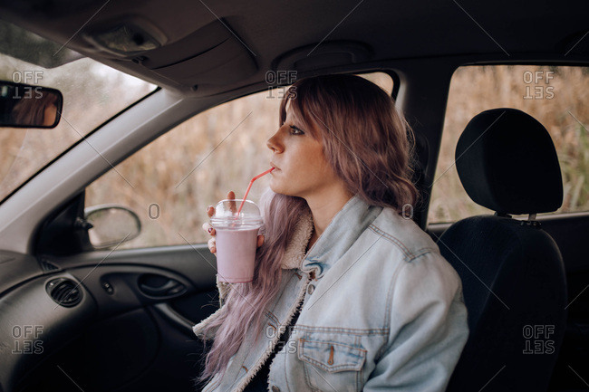 Side view of young modern woman with pink hairstyle drinking smoothie from plastic cup with straw sitting in car