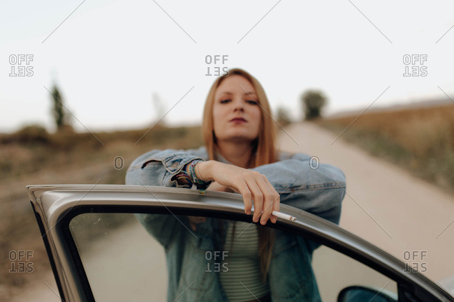 Confident woman in denim jacket standing with cigarette at car door looking at camera in country