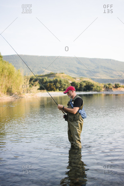Side view of man in waders and cap fishing in tranquil water with picturesque landscape