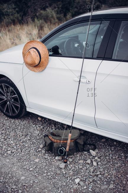 Set of fishing stuff located near modern white car in wonderful countryside