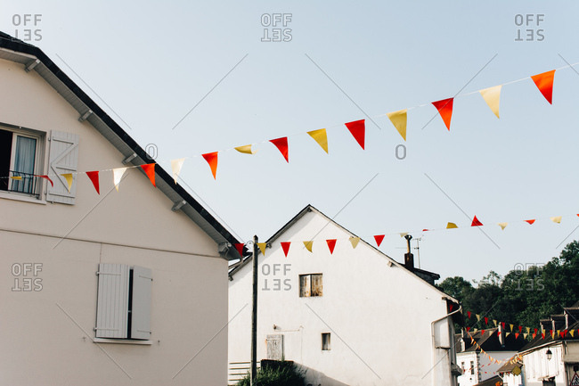 Colorful triangle flags hanging among lovely suburban cottages against clear blue sky