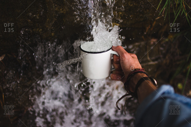 Close-up shot of hand of anonymous man holding mug under fresh water of cold water source in nature