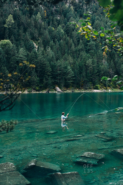 Back view of man standing in clean water of beautiful lake and fishing