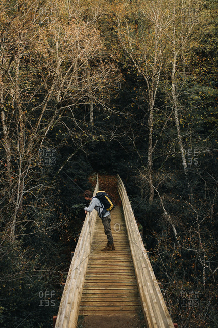 Side view of young guy with backpack leaning on railing of ancient bridge near autumn forest