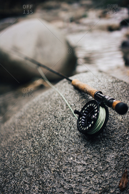 Close-up shot of nice fishing rod lying on smooth boulder near beautiful river