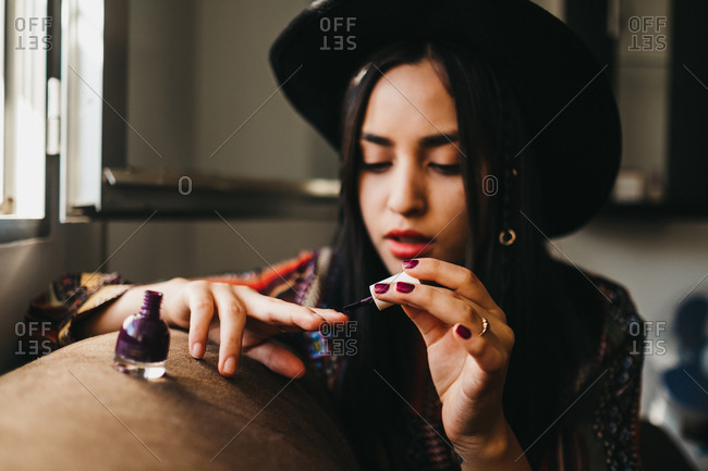 Pretty young female in stylish outfit using brush to apply nail polish while sitting on comfortable sofa at home