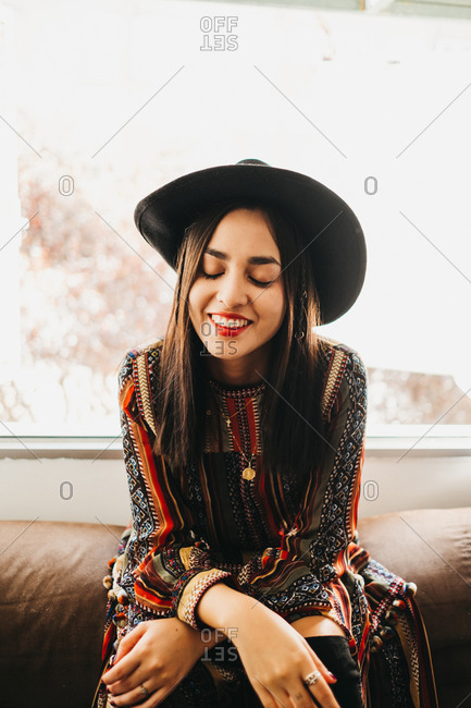 Attractive young lady in stylish outfit smiling and keeping eyes closed while sitting on back of soft sofa near window