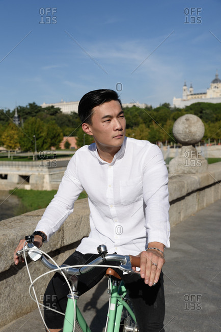 Handsome Asian guy looking away while riding bicycle along path in beautiful park