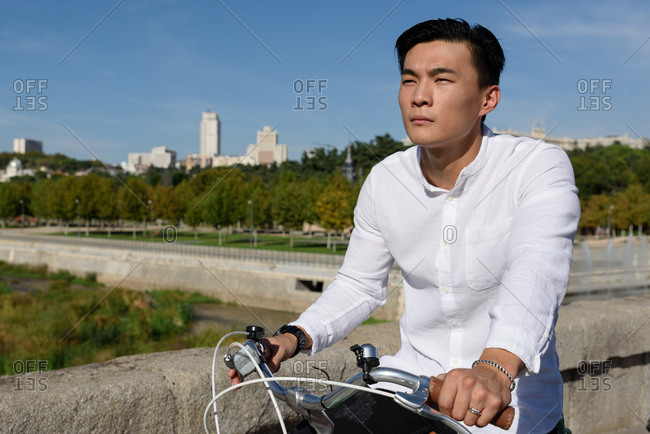 Asian man riding bicycle in park stock photo - OFFSET