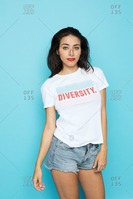 Attractive�woman�with red lips in white shirt and jeans shorts looking at camera on blue background