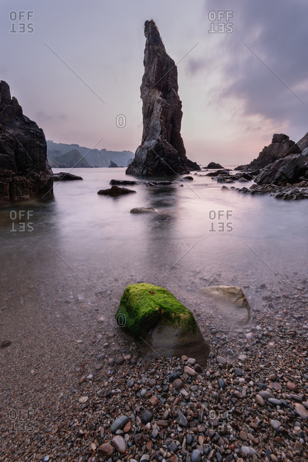 Rough rocks lying on shore near calm sea water during magnificent sunset