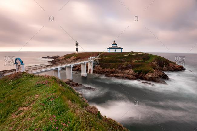 Magnificent view of small bridge crossing majestic river near sea in morning