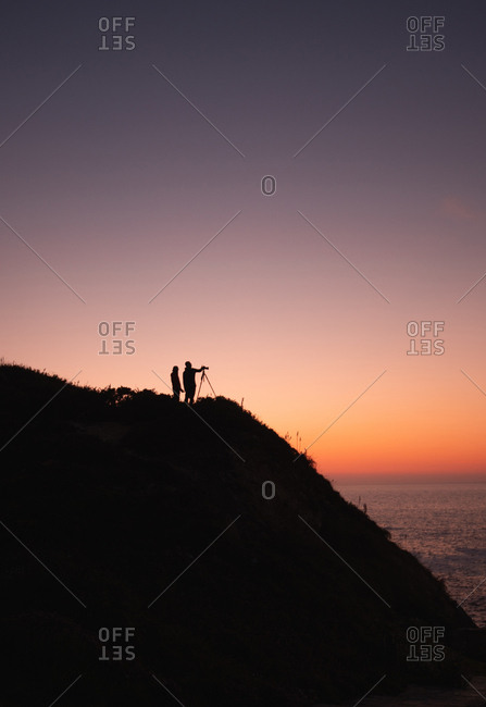 Silhouette of two people with camera on tripod standing on coast near calm sea on background of cloudless sunset sky