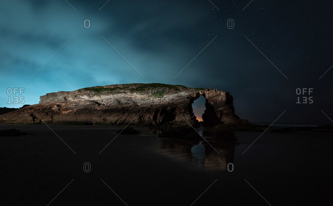 Wonderful arched cliff located near calm sea on spectacular night in beautiful nature