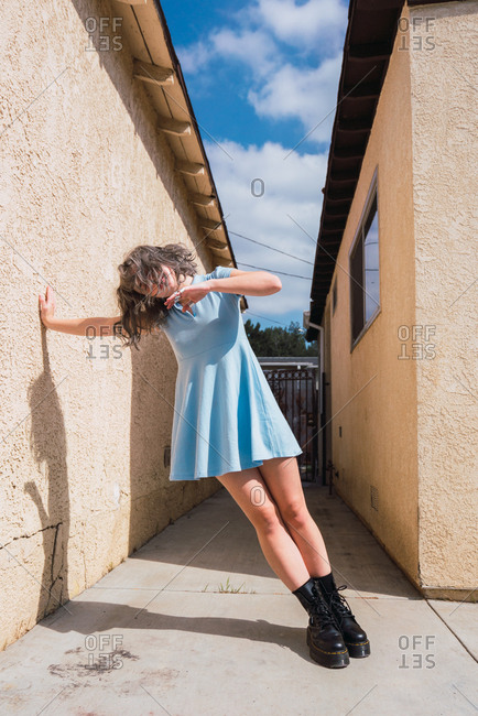 Adorable young woman with gray hair leaning on wall of suburban house while standing on street on sunny day