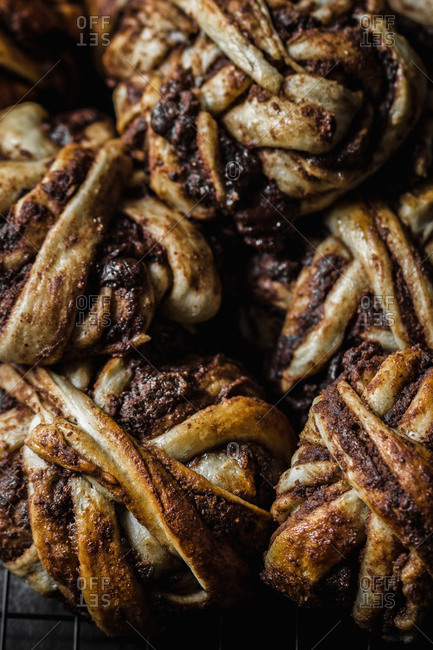 Close-up shot of bunch of delicious chocolate buns lying on metal grating in dark room