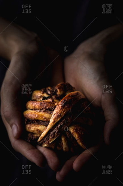 From above shot of crop hands showing small chocolate bun to camera in dark room