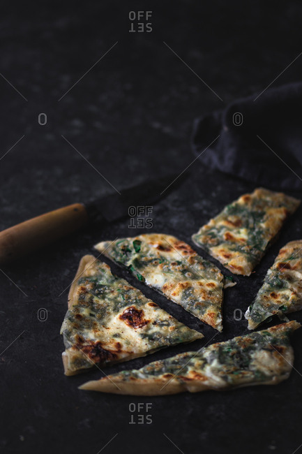 Slices of fresh lime lying on pieces of delicious gozleme on tabletop in dark room