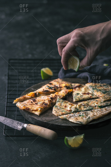 Hand of anonymous person putting pieces of fresh lime on board with slices of tasty gozleme near knife and grating