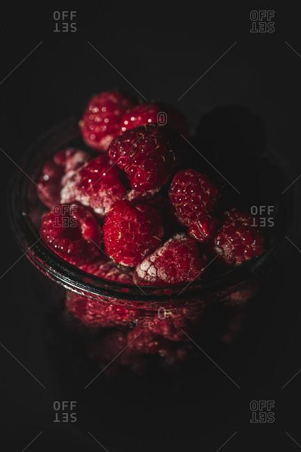 Close-up shot of yummy ripe raspberries lying in glass jar in dark room