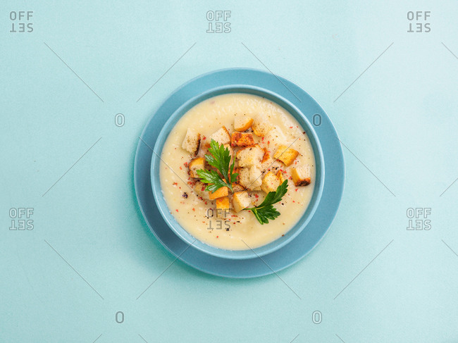 Cauliflower potato soup puree in blue bowl on blue minimalistic background. Top view flat lay. Copy space