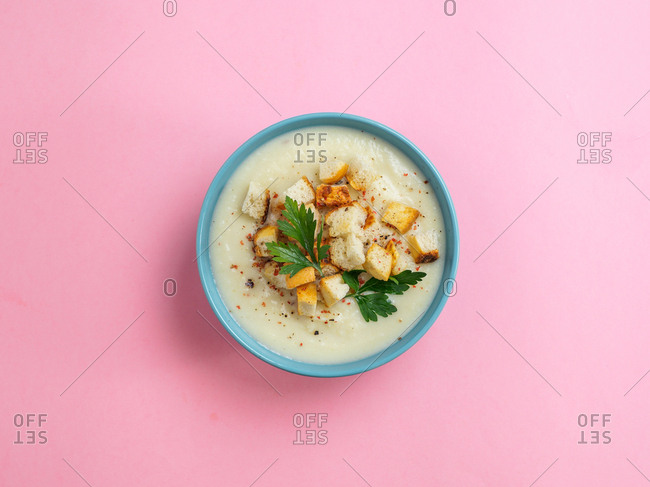 Cauliflower potato soup puree with croutons in blue bowl on pink minimalistic background. Top view flat lay. Copy space