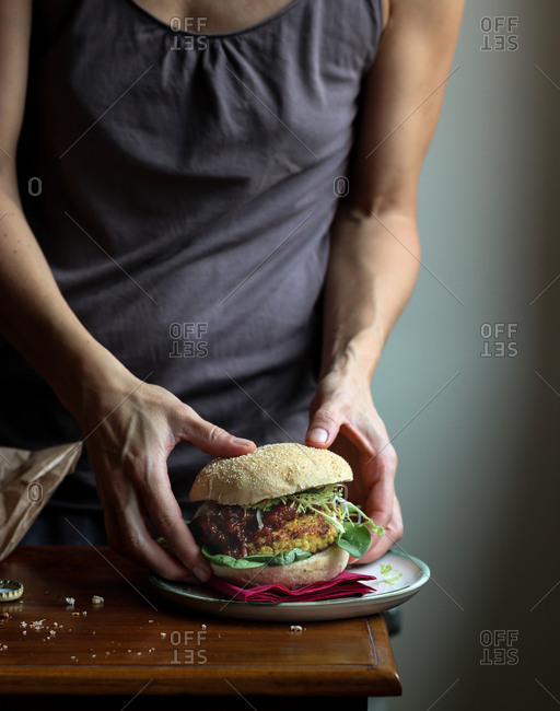 Crop woman enjoying beer and veggie burger