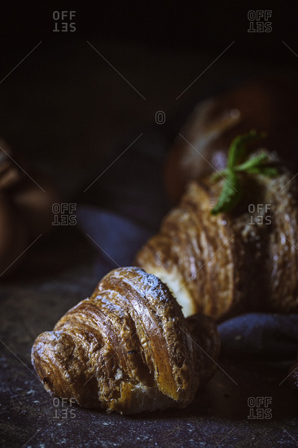 Freshly baked buns with almonds, croissants an brioche, on dark background