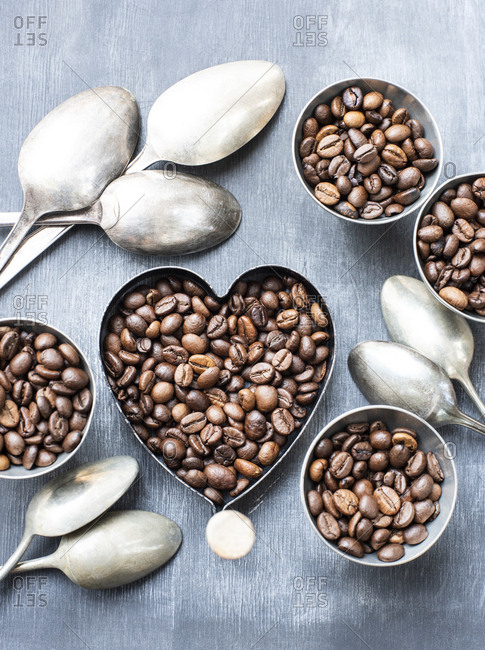 A bowl in the shape of a heart filled with coffee beans