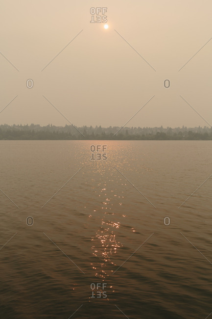 Hazy, smoky air and sun over calm lake water at dusk, Green Lake, Seattle, Washington, USA.