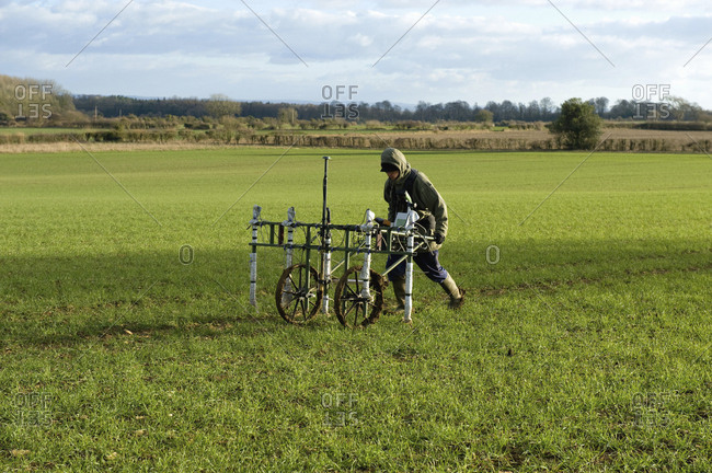 A geophysicist pushing a trolley with ground mapping sensors, creating a geophysical survey of the subsoil in a field.
