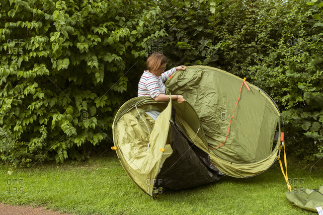 A woman putting up a green pop up tent in a sheltered spot by a tall hedge.
