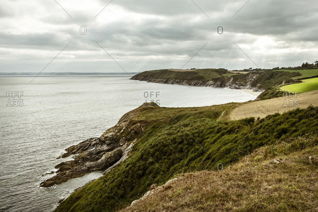 View along the ocean coastline, headlands and bays, cliffs and landscape sloping towards the water.