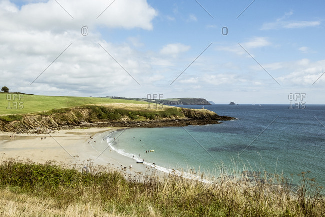 View over a sandy beach and cliffs in summer, a few people, clear shallow water and calm sea.
