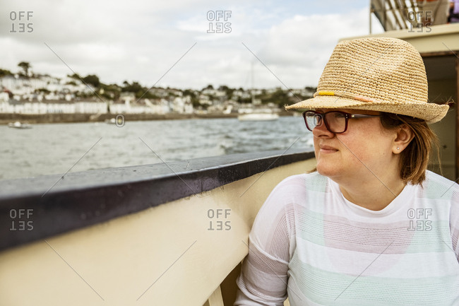 A woman in a straw hat on a boat looking out to the town on the shore on an overcast day.