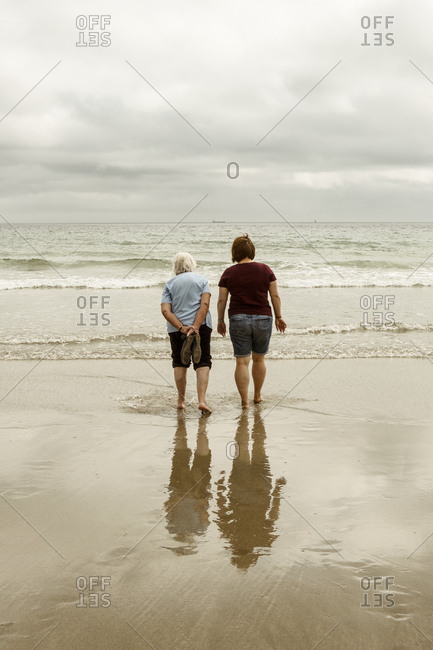 Rear view of a grey haired elderly woman and a younger woman paddling with shoes off in shallow waves on a sandy beach.