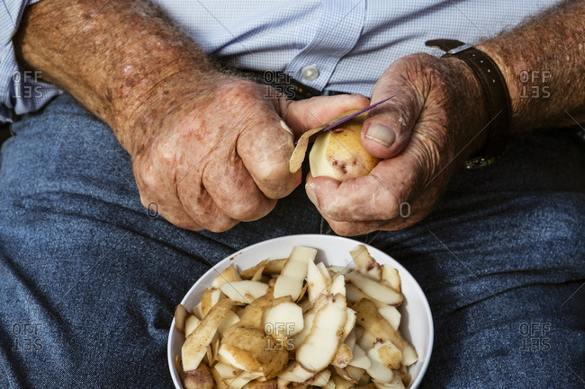 A man seated using a sharp knife to peel potatoes.