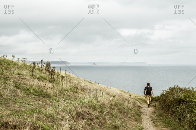 Rear view of a man in walking boots with a rucksack, walking along a coastal path, and a sea view.