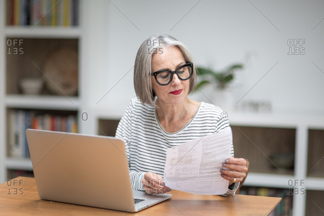Mature adult female paying bill online using a laptop