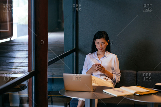 Pretty Asian woman freelancer sitting at modern cafe and typing on her cell phone.