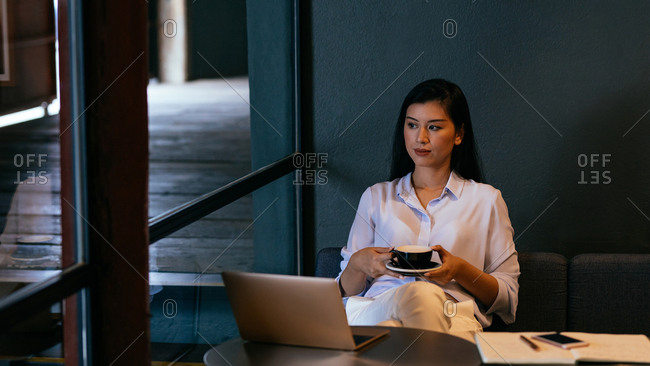 Beautiful serious Thai woman freelancer sitting at cafe and drinking coffee.