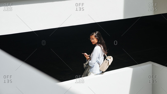 Beautiful Thai woman standing between the building floors and typing on her cell phone.