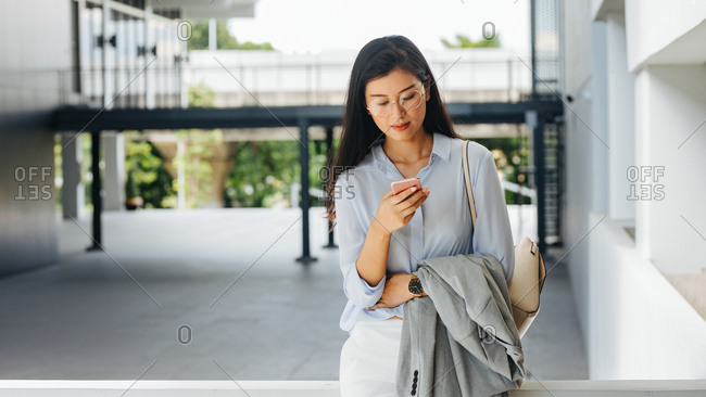 Elegant pretty Asian businesswoman standing outdoors and typing on her smart phone.